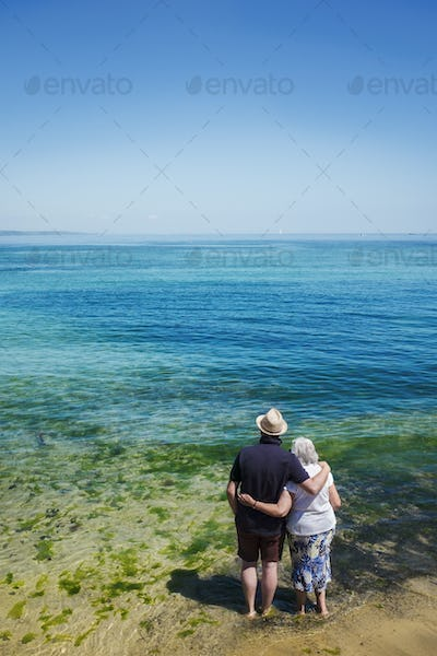 Rear view of elderly couple standing with arms around shoulders looking out to sea across the vivid