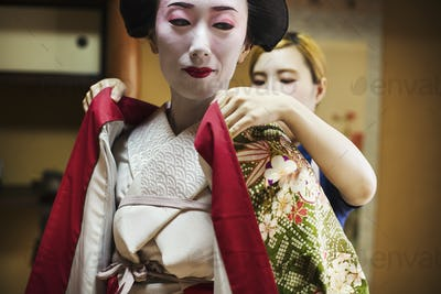 A woman being dressed in the traditional geisha style, wearing a kimono with white face makeup with