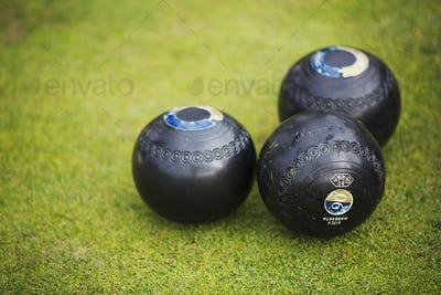 Three round wooden black lawn bowls on a smooth playing surface.