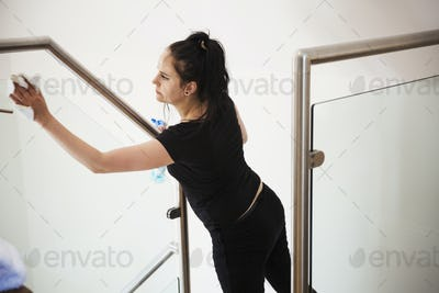 Woman standing on a staircase, cleaning a glass pane and banister rail.
