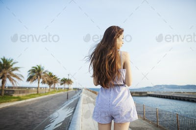 Back view of young woman with long red hair standing in open space by a road on the coast.