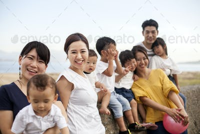 Group portrait of Japanese families with young children on promenade by ocean, smiling at camera.