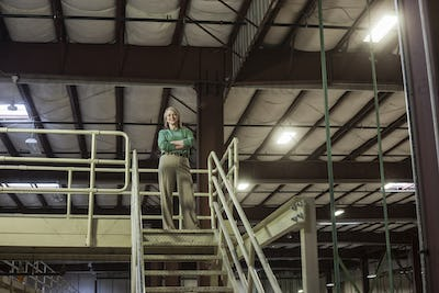 Portrait of a caucasian female executive in a warehouse distibution facility, with a products stored