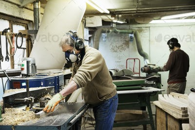 Man standing in a carpentry workshop, wearing a respirator and hearing protector, working on a piece