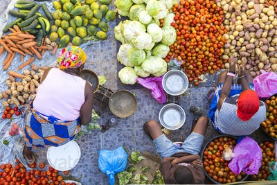 High angle view of vendors selling a selection of fresh vegetables on a street market.