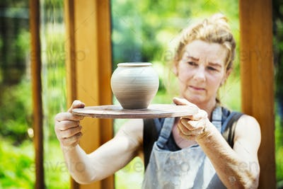 A potter examining a hand thrown pot, wet clay slip, rounded vase with tapering sides.