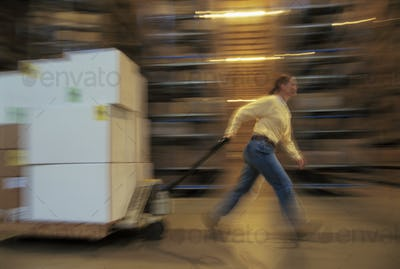 Warehouse employee moving a pallet of products in cardboard boxes in a large distribution warehouse.