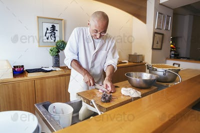 A chef working in a small commercial kitchen, an itamae or master chef slicing fish with a large