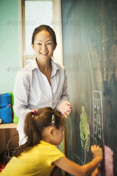 A child writing on the chalkboard and a teacher beside her.