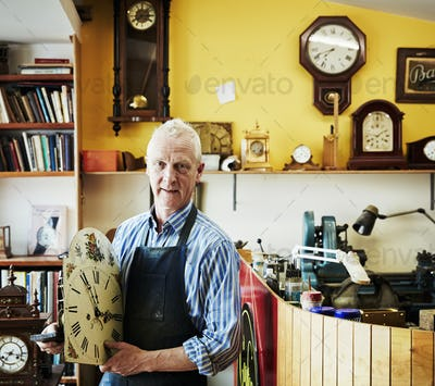 A clock repairer holding an antique clock face in his workshop.