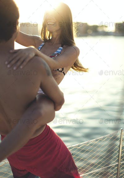 A man holding a young woman and swinging her around on a boat deck.