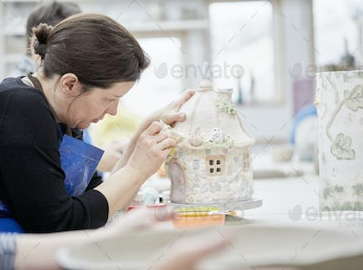 A woman working on a decorated pottery cottage with a sponge, decorating or finishing a piece.