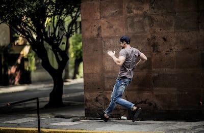 A man dancing on a city sidewalk.