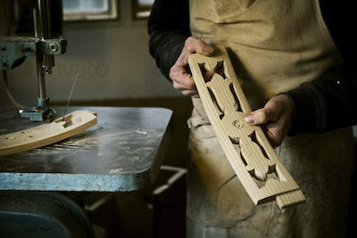 A man working in a furniture maker's workshop holding shaped carved chair back struts.