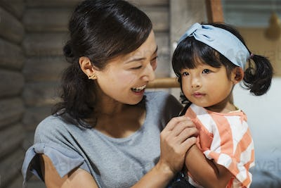 Smiling woman holding young girl with black pigtails wearing blue hairband.
