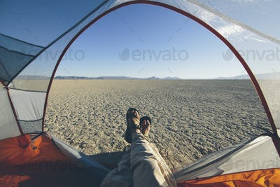 Man reclining in camping tent, expansive desert and playa in distance, Black Rock Desert, Nevada