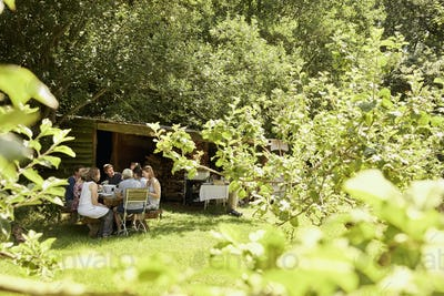 A group of people eating a meal outdoors in summer in the shade of trees in a garden.