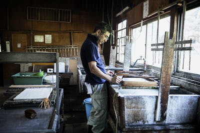 Japanese man in a workshop, holding a wooden frame with pressed pulp, making traditional Washi