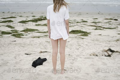Rear view of a girl with blond hair in a white t-shirt, standing on a sandy beach.