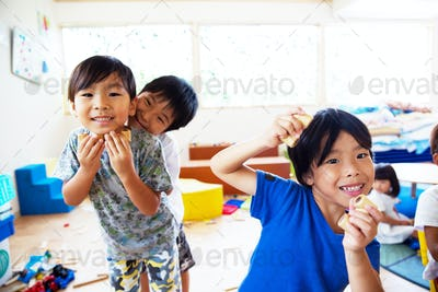 Three young children in a Japanese preschool, looking at camera and pulling faces,smiling.