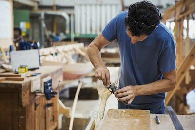 Man standing in a boat-builder's workshop, working on a wooden oar.