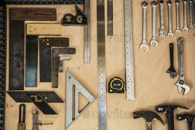 Close up of a selection of tools on a wall in a woodworking workshop.