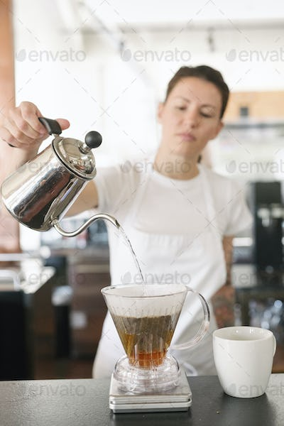 Woman wearing a white apron standing in a coffee shop, making filter coffee.