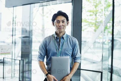 Businessman wearing blue shirt standing indoors by glass wall, holding laptop, looking at camera.