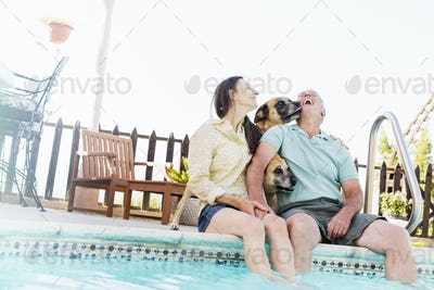 A couple sitting on the edge of a swimming pool, with their dogs.