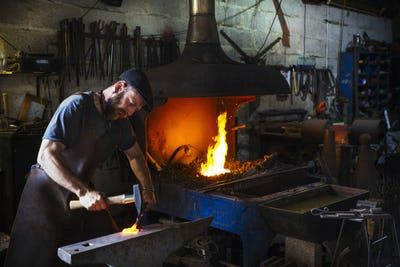 A blacksmith strikes a piece of red hot metal on an anvil with a hammer in a workshop.