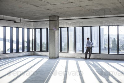 Caucaisan businessman carrying plans and looking at a new empty raw office space.
