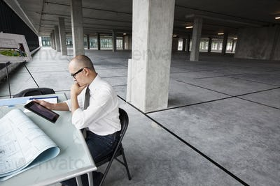 Asian architect woking on workspaces in a new raw office location.