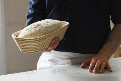 Close up of a baker holding a freshly baked loaf of white bread in a rattan proofing basket.
