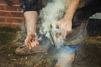A farrier shoeing a horse, bending down and fitting a new horseshoe to a horse's hoof. Steam rising.