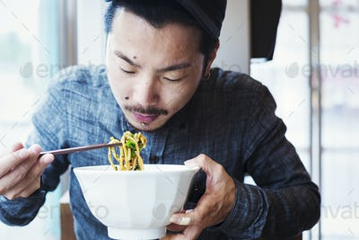 A ramen noodle cafe in a city.  A man seated eating ramen noodles from a large broth bowl.