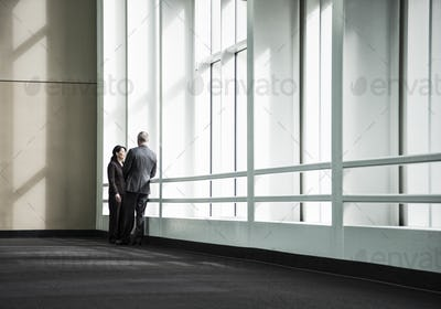 Businessman and woman meeting in a large glass covered walkway