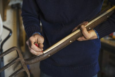 Man standing in a workshop, holding a pencil, working a new wooden shaft for an old metal tool, a