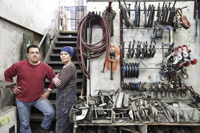 Man and woman mixed race team of workers in a large sheet metal factory