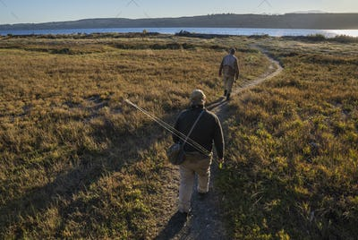 Two fly fisherman walking a well worn trail to a salt water beach on Indian Island in northwest