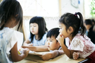 Group of children sitting at a table in a Japanese preschool.