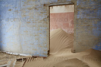 Interior of an abandoned building full of sand.