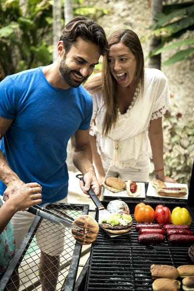 A couple standing at a barbecue cooking food.