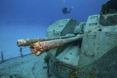 Diver near the gun turret on a shipwreck, which was intentionally sunk as an artificial reef.