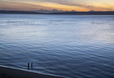 A view from above of a guide and a fly fisherman at the water's edge, fishing for salmon and sea run