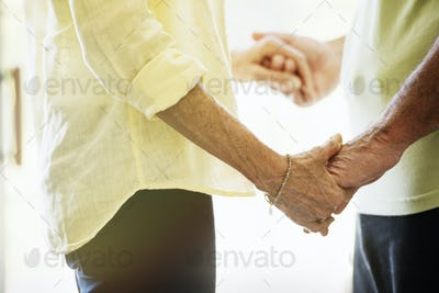 Close up of a senior couple holding hands, facing each other.