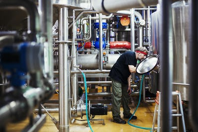 Man working in a brewery adjusting and checking the machinery which transfers the brewed beer around