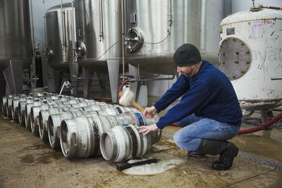 Man kneeling and hammering in a peg into a metal beer keg. Large fermentation tanks.