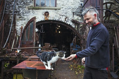 Blacksmith standing outside his workshop, feeding a cat.