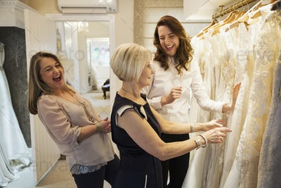 Three women in a wedding dress boutique looking at a rail of white bridal gowns, with lace and