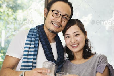 Portrait of smiling woman and man wearing glasses standing side by side, looking at camera.